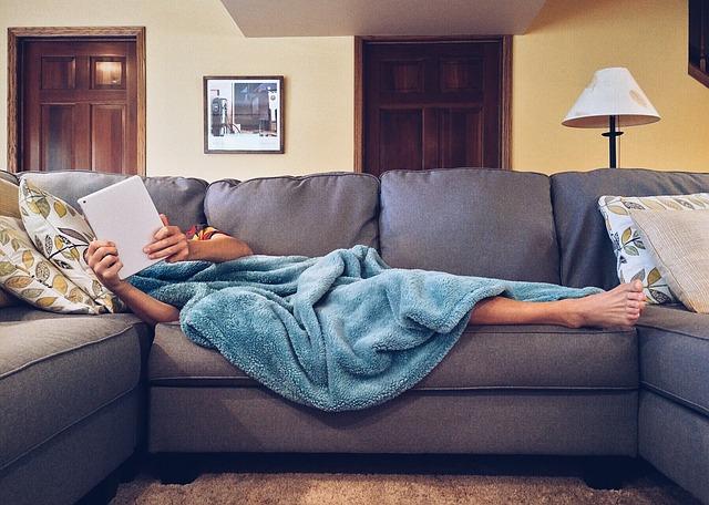 布製のソファーで寝る人