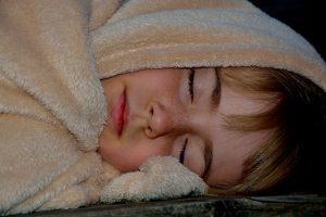 ふわふわの毛布で寝る子供