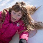 雪山で遊ぶピンクのダウンを着た女の子