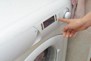 洗濯機のスタートを押す手