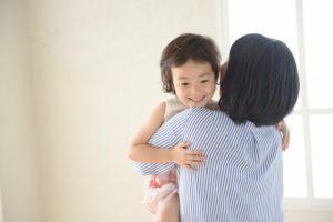 母親に抱きかかえられる娘