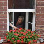 窓を掃除する老婆