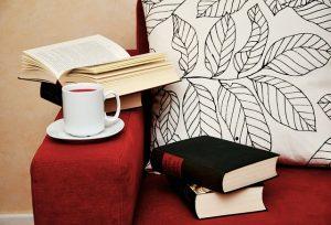 ソファーの肘掛けに置いたコーヒーと本
