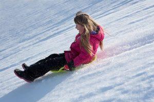 雪山でダウンを着て遊ぶ女の子
