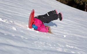雪山でこけるダウンを着た少女