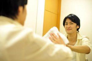 洗面所の鏡を拭く旦那