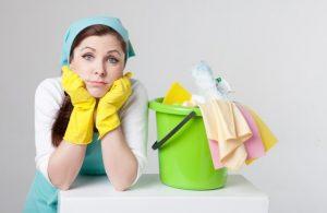 掃除用具を持って方法に悩む女性